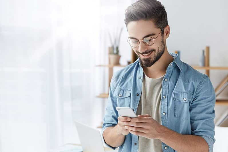 Man smiling while looking at smart phone
